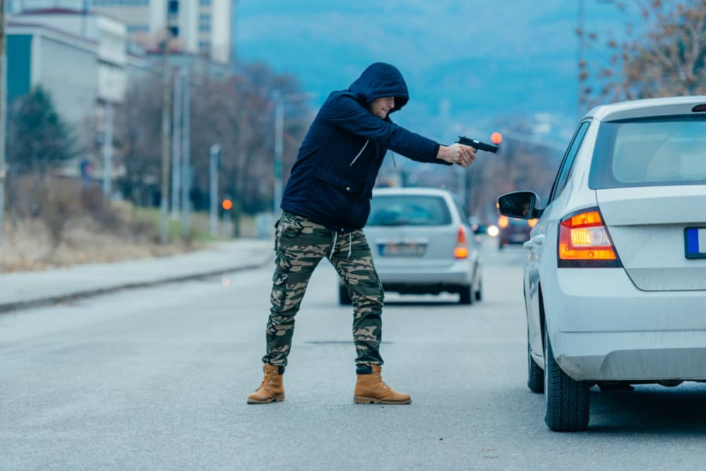 Car hijacker with a gun trying to rob a guy which is sitting in his car. Gorgev / Shutterstock.com